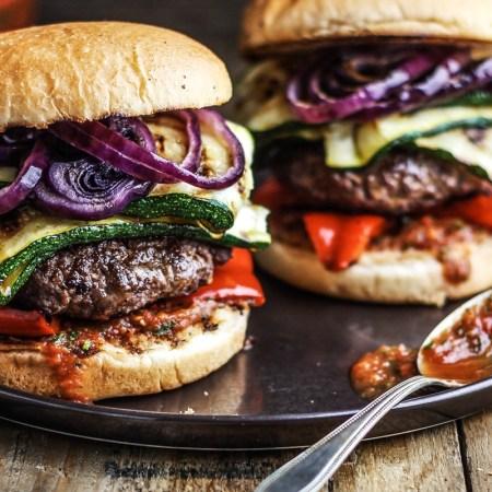 zwei Burger mit Grillgemuese und Rinderhack-Pattie auf schwarzem Teller und Holztisch