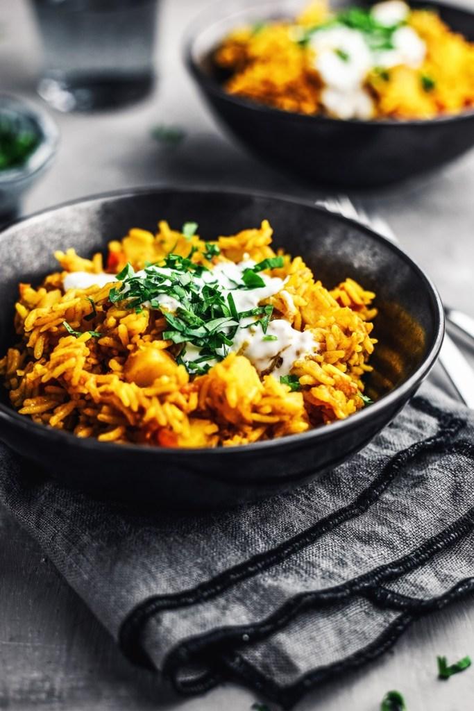 schwarze Schale mit One-Pot-Reis mit Kurkuma und Tomaten.
