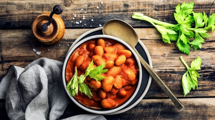Teller mit weißen Bohnen in Tomatensauce auf Holztisch
