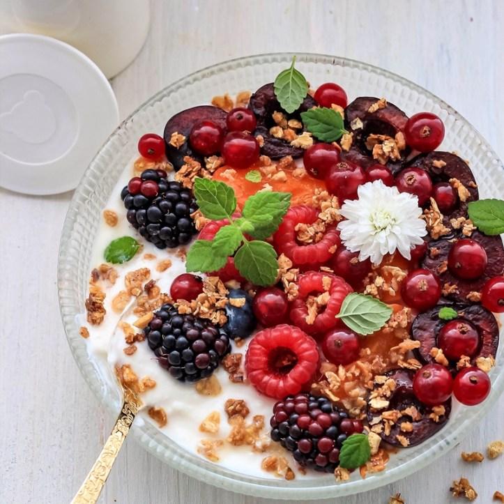 Selbstgemachter Joghurt mit Fruechten und Blueten dekoriert.