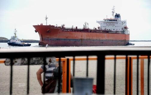 Een schip wordt door een sleepboot naar de sluizen van IJmuiden getrokken.