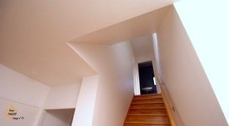 Photo de l'escalier inscrit dans le plafond d'entrée