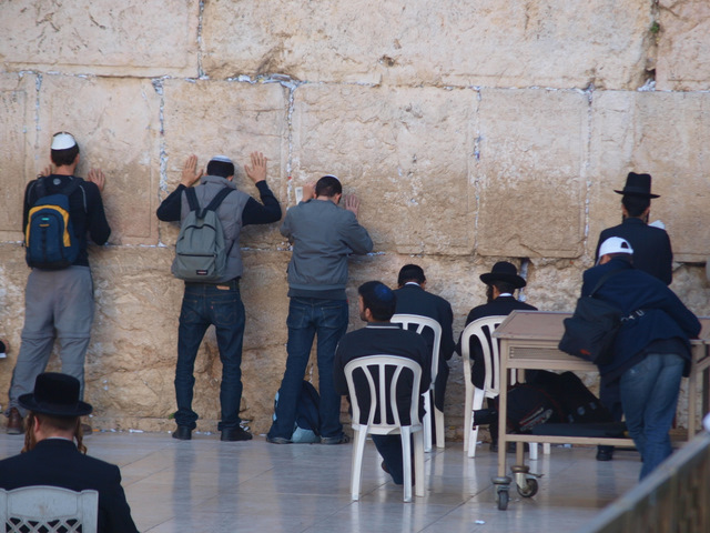 Men praying at the Western Wall, also known as the Wailing Wall