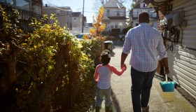 Father and daughter holding hands walking with bucket