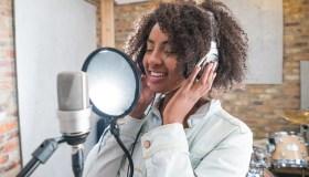Woman singing at a recording studio