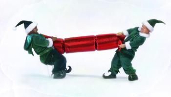 Two male 'elves' pulling large christmas cracker (digital enhancement)