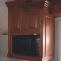 Alderwood kitchen cabinets with hidden microwave can be designed into