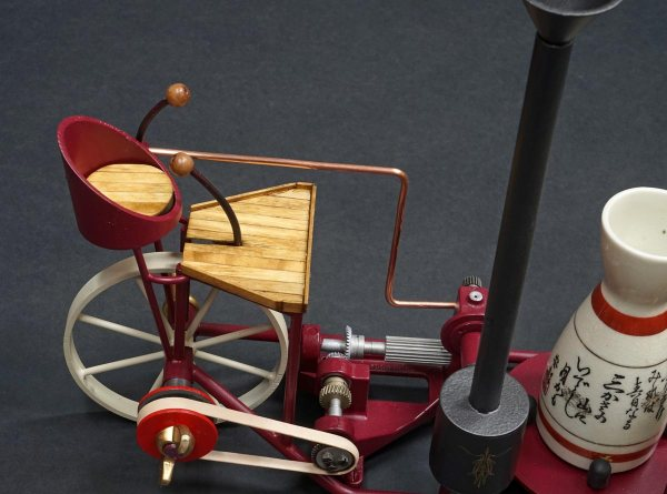 """a closeup of the intricate gears and engineering featured in the metal sculpture """"Seishu Cart"""" a metal work art piece that doubles as a sake decanter and glass holder or bar cart"""