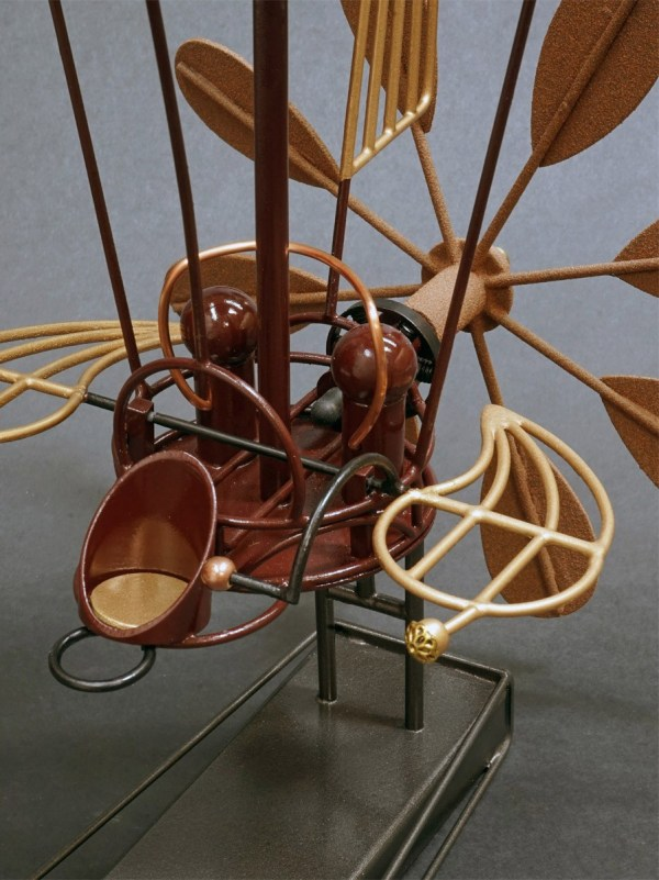 """A closeup picture of the metal sculpture """"Rapid Flyer"""" a handcrafted metalwork depiction of a propeller driven dirigible"""