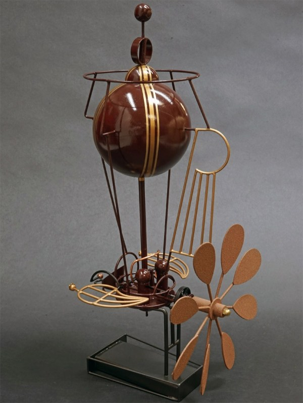 """the left side of the metal sculpture """"Rapid Flyer"""" a handcrafted metalwork depiction of a propeller driven dirigible"""