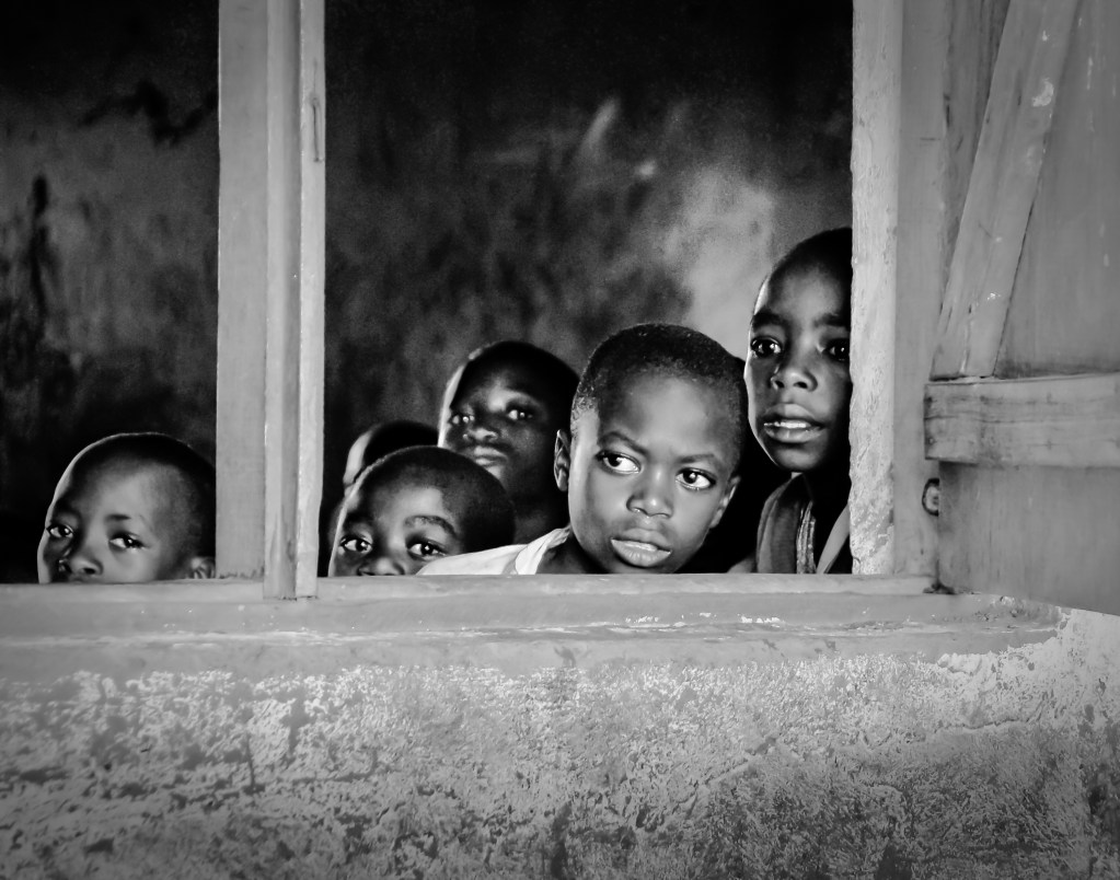 Young African school children peer through the open of their classroom.