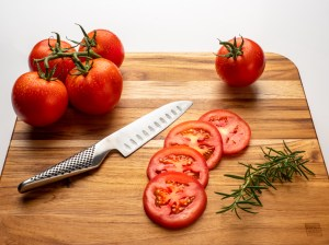 Sliced Tomatoes - High Key Still Life Photograph - Tomatoes on a cutting board with a knife and sprig of rosemary