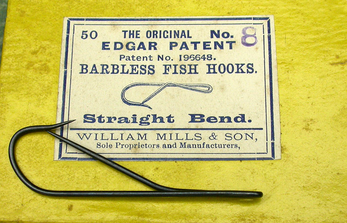 "12. Edgar Patent Barbless Hooks, #8, straight bend, blued, patent No. 196648, made by William Mills & Son, sole proprietors and manufacturers. About 2 1/8"" long. In the late 1800's, discussions raged over the merits of ""barbless"" hooks. The arguments were focused generally on the point of fish hookup. In other words, the relative ease of penetration of a needle point hook sans barb vs. a more traditional barbed hook. Fish mortality also entered into the discussions but was a subordinate line of discussion. It seems the more things change, the more they stay the same as these discussions continue to this day. There was one fellow by the name of Butler Edgar who developed and patented the so called ""Edgar Barbless Hook"". The idea was simple enough, have a needle point barbless hook for ease of hook up and another opposing needle point to prevent breaking off a fish. They were made by the Wm Mills & Son Company (The Bate hook company). Later, they were made and sold by other companies. Again, you can read more about this in Todd Larson's book ""The History Of The Fish Hook In America""."