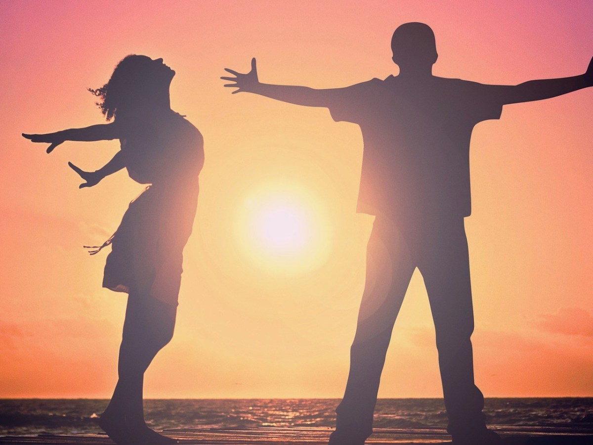 Man and woman with outstretched hands toward the sun