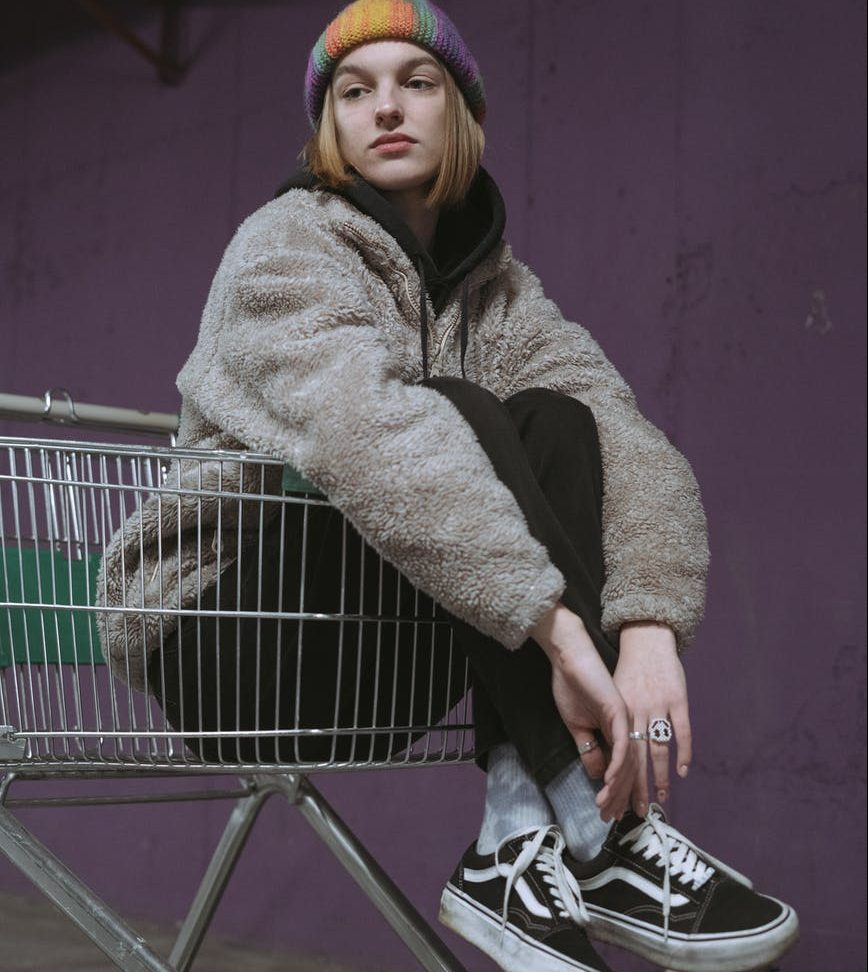 woman in gray sweater and blue denim jeans sitting on gray shopping cart