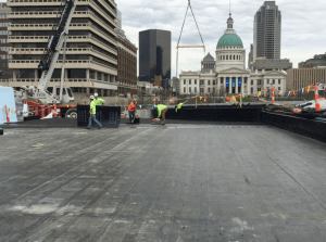 After two layers of modified bitumen sheet waterproofing were installed, crews apply a coat of adhesive to adhere the asphaltic protection board.