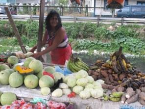 An dem Marktstand neben dem stinkenden Kanal, verkauft die Frau Melonen und andere Früchte.