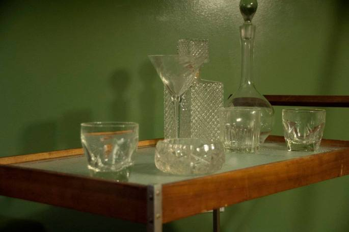 A beautiful old dining cart with old glasswear sitting atop.
