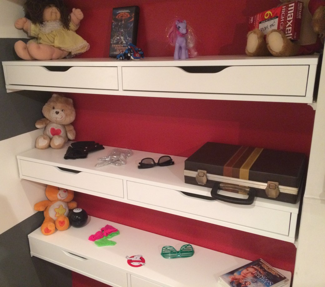 Three shelves with a variety of toys, clothing and movies from the 1980s