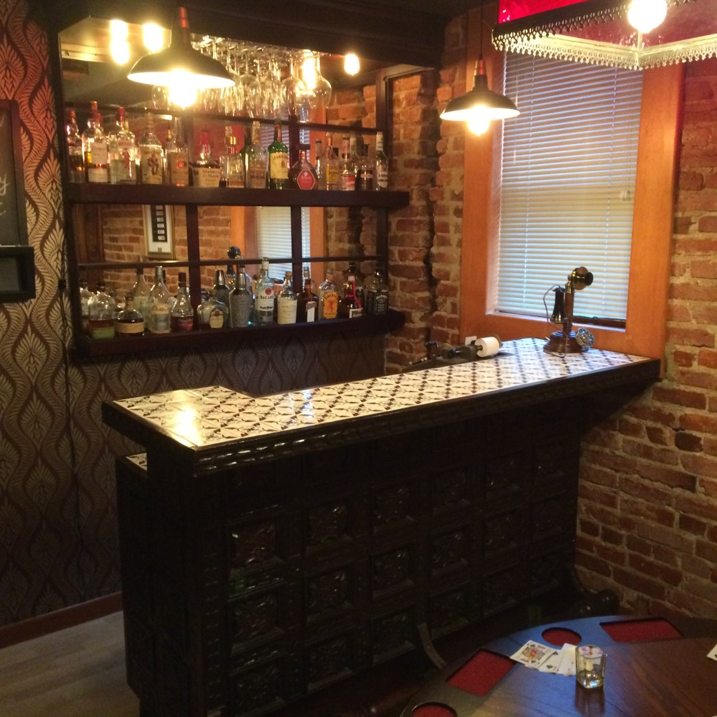 An old bar with a rotary phone on it. Behind the bar is a mirrored wall lined with liquor bottles.