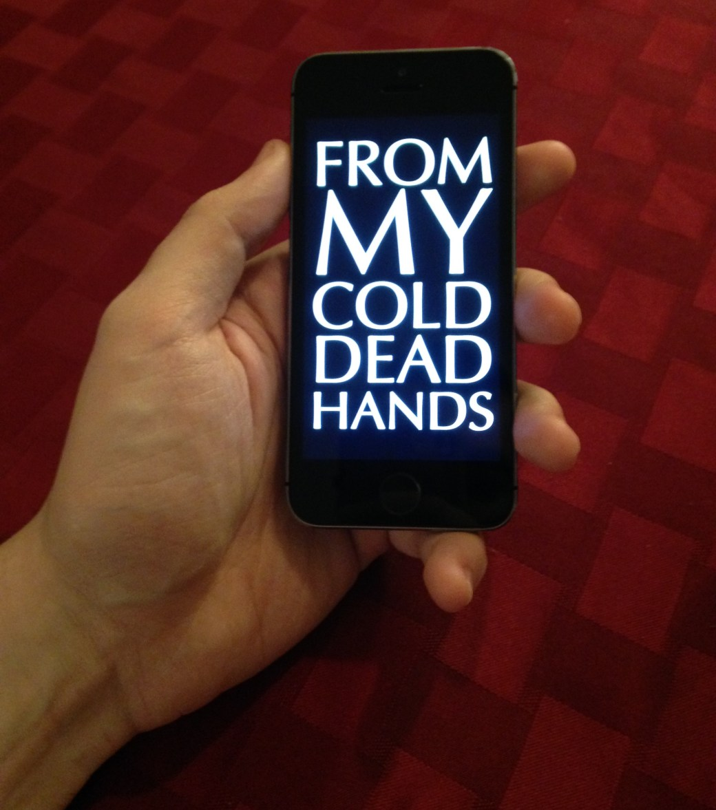 """A closeup of a hand holding an iPhone. The iPhone's screen says, """"FROM MY COLD DEAD HANDS"""" in a dramatic font."""