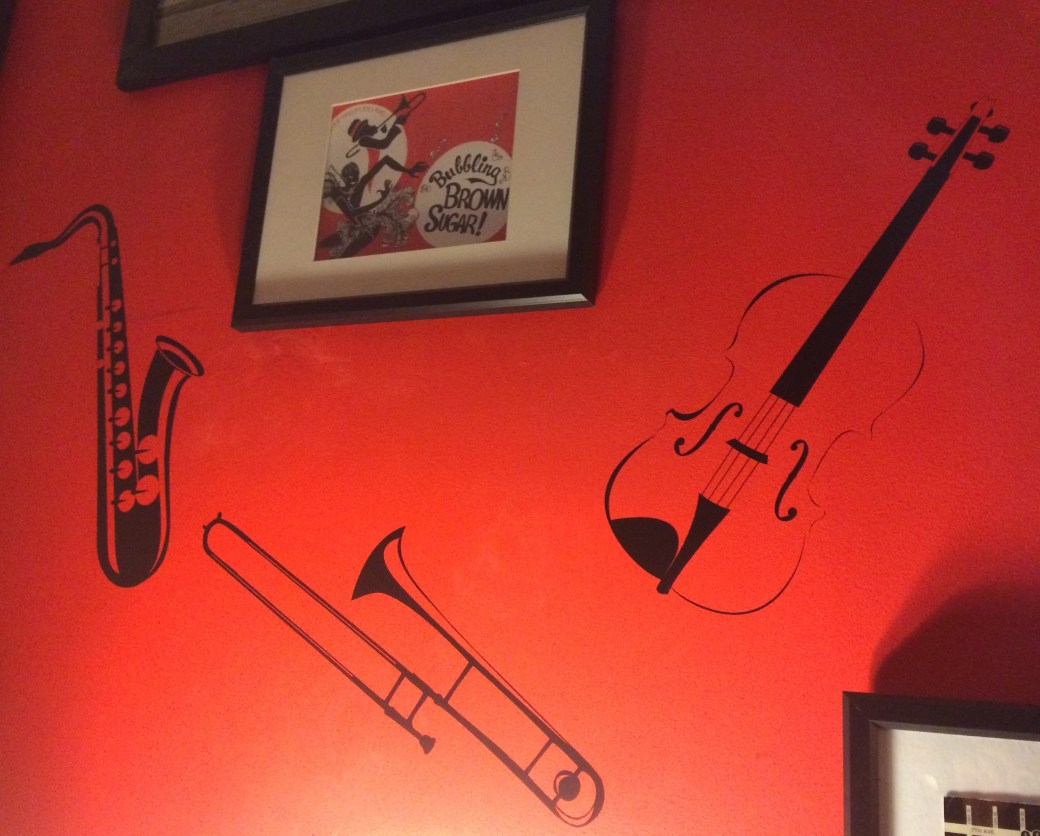 Red wall with a violin, trombone, and saxophone painted on it.