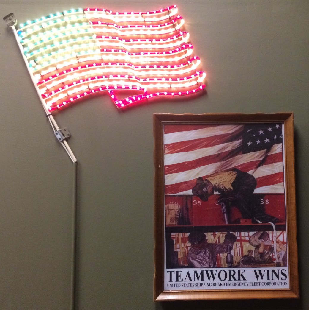 """Photo of an illuminated LED American flag beside a military propoganda poster that says, """"Teamwork wins"""""""