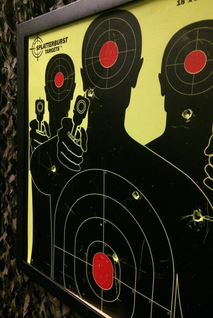 Photo of a shooting target. The target depicts the silhouette of three men with pistols. The target has a number of bullet holes in it.