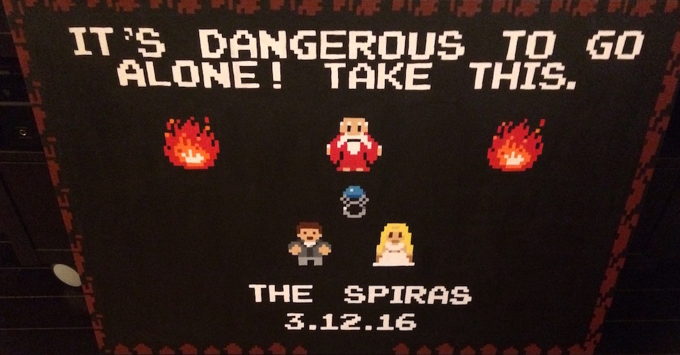 """8 bit painting inspired by Zelda - It says, """"It's dangerous to go it alone! Take This. The Spiras 3-12-16."""" It depicts an old man in a fire-lit cave giving a ring to a couple dressed for a wedding."""
