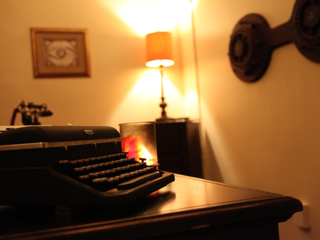 Warmly lit image of a typewriter on a desk.
