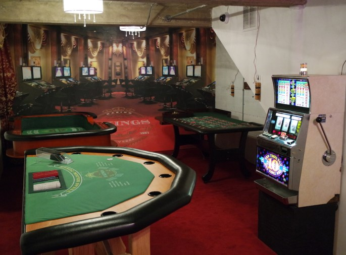A casino including a slot machine, roulette, craps, and blackjack tables. The walls are rigged with explosives.