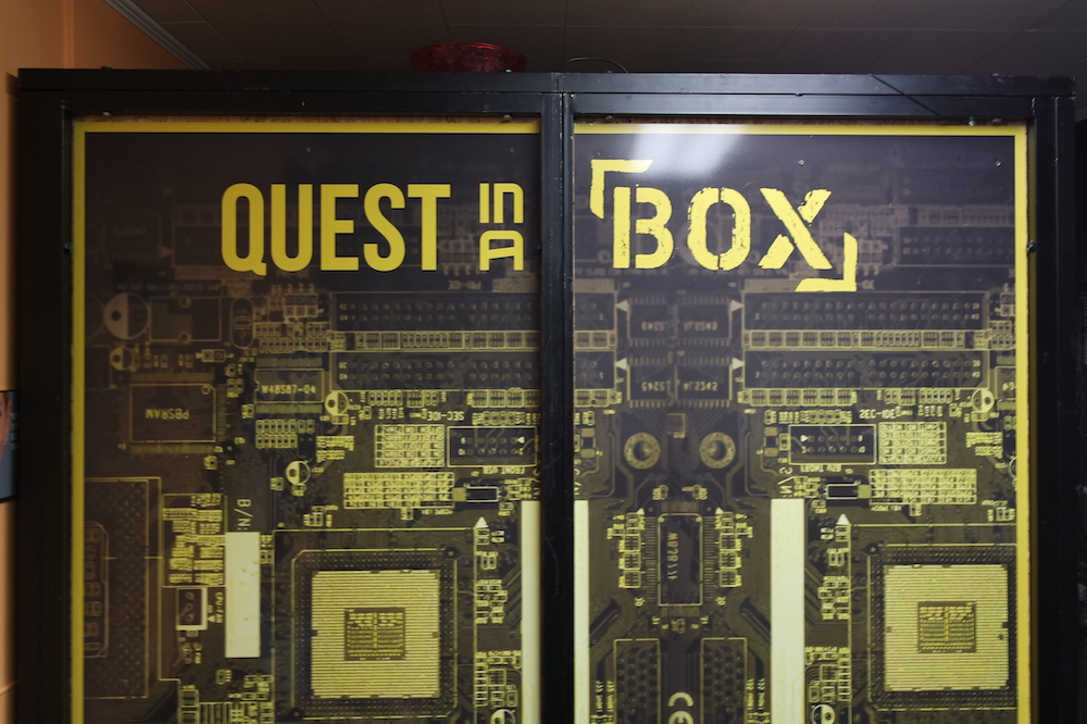 "An odd box that nearly reaches the ceiling. It says, ""Quest in a Box"" on its side."