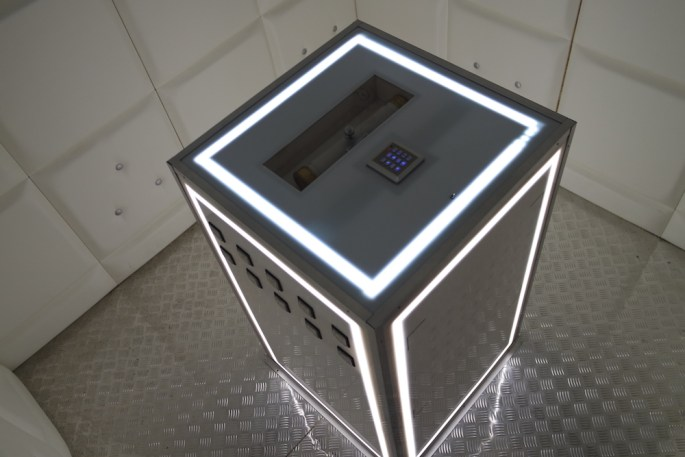 Interior shot of the cube. It has padded walls, a steel floor, and a console in the middle. Everything glows white.
