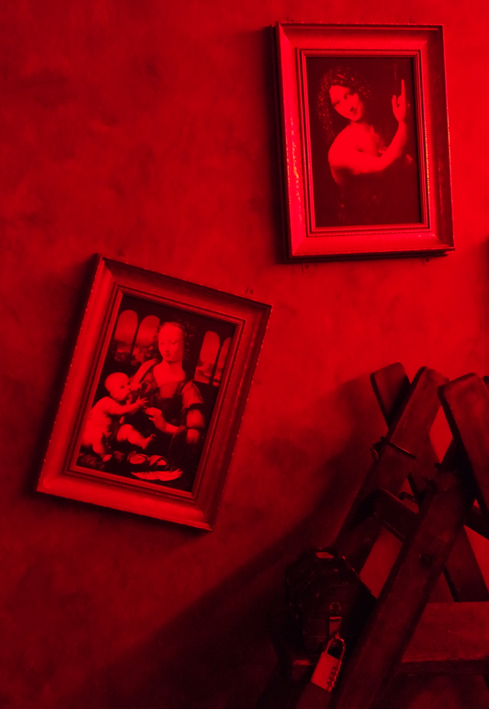 A room lit in red, two Leonardo Da Vinci photos hang on the wall. A shelf holds a small locked box.