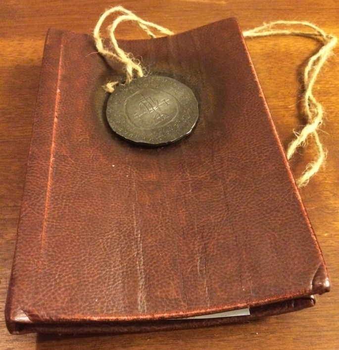 A leather bound book with a metal medallion with intricate inscriptions on its face resting atop the book.