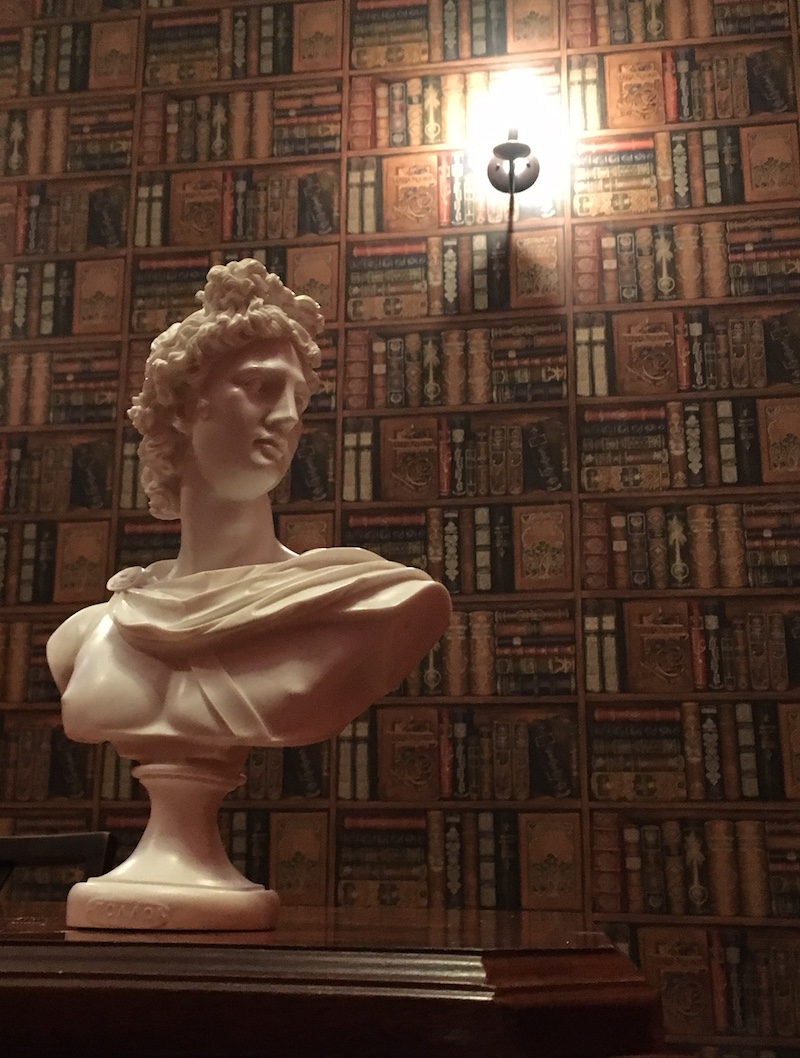A greco-roman bust sits upon a wooden desk, a wall of books rests behind it.