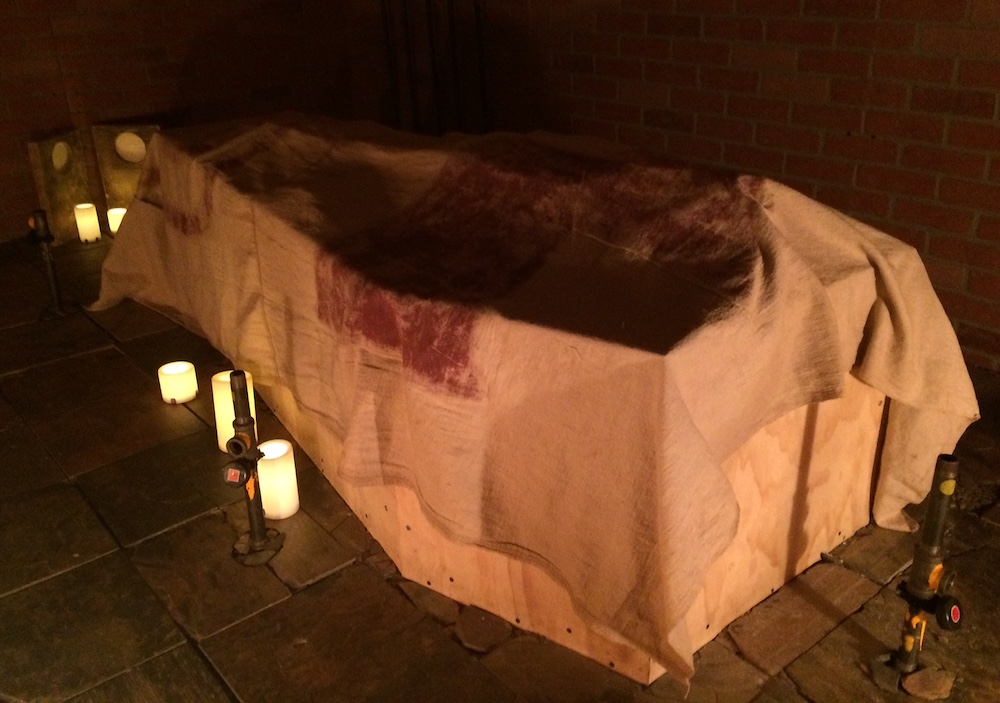 A coffin drapped in a white cloth in a dark, crypt.