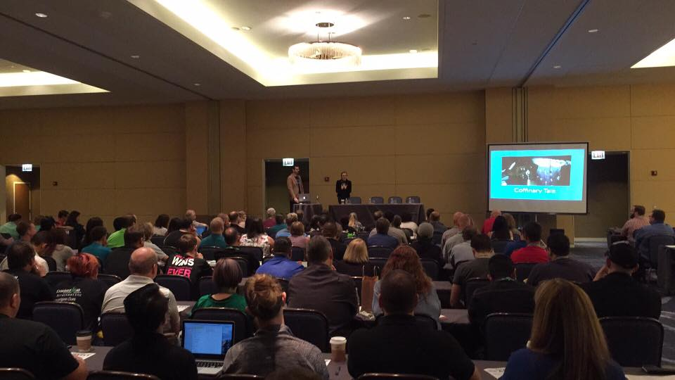 Image of a packed lecture hall with Lisa and David on stage presenting.