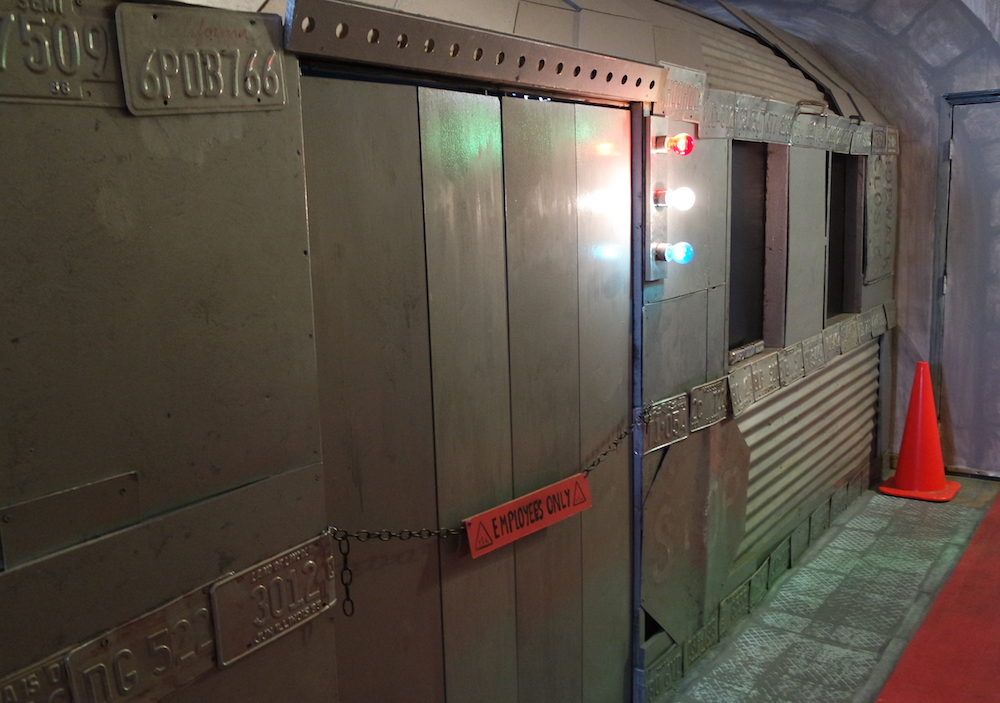 External shot of the recycled and recialmed railcar. A silver train car made from wood, corrigated aluminum, license plates, and other found objects.