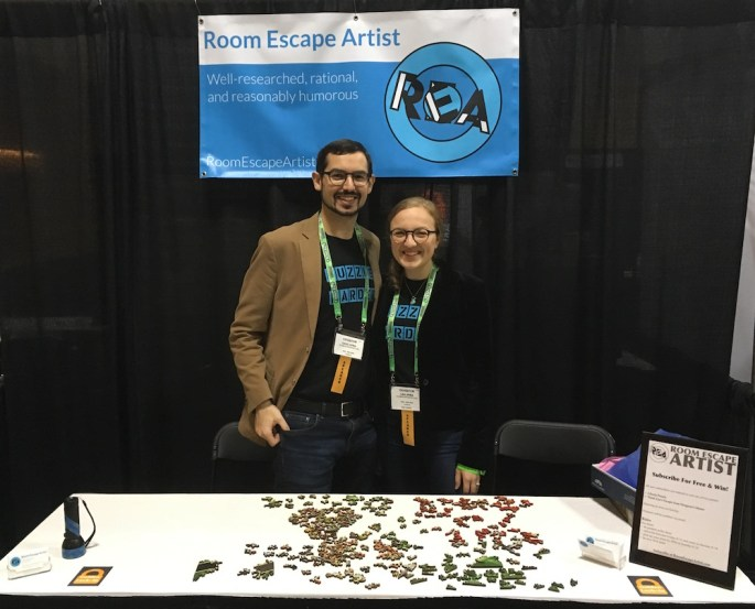 """Lisa and David standing behind their booth at the conference. Their banner in the background, and an unsolved puzzle in the foreground. They are wearing their """"Puzzle Harder"""" t-shirts."""