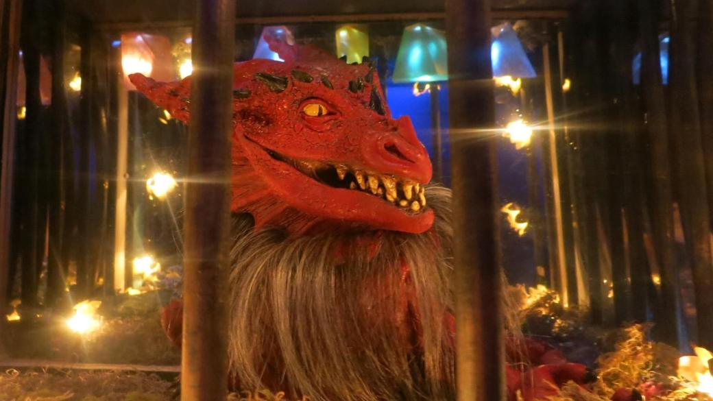 In-game image of a dragon locked behind bars.