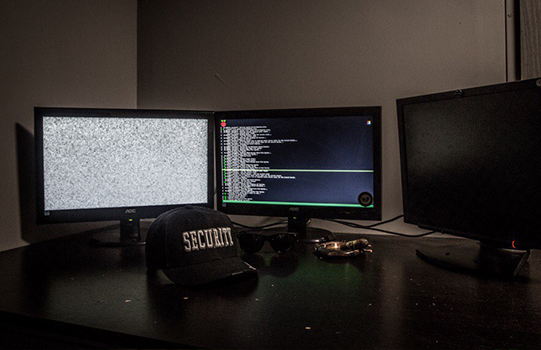 "A desk with three computer monitors on them. In front of the monitors is a baseball cap that reads, ""security."""