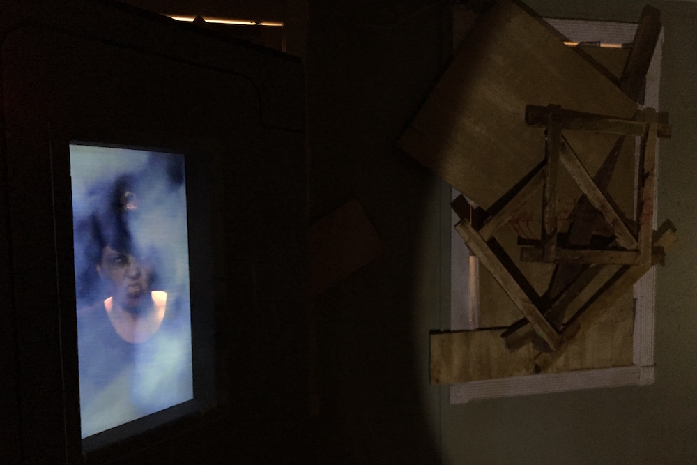 A zombie locked away in a chamber beside a boarded up window.