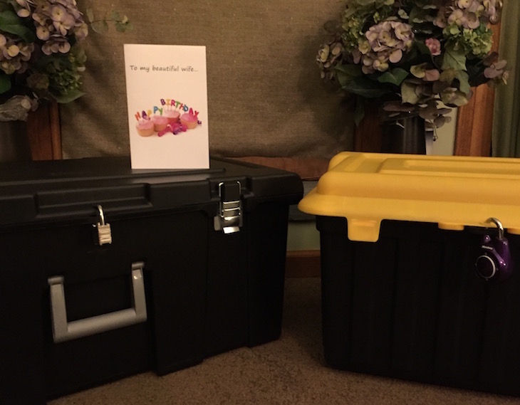 """Two large locked boxes. One has a birthday card resting on it that reads, """"To my beautiful wife... happy birthday."""""""