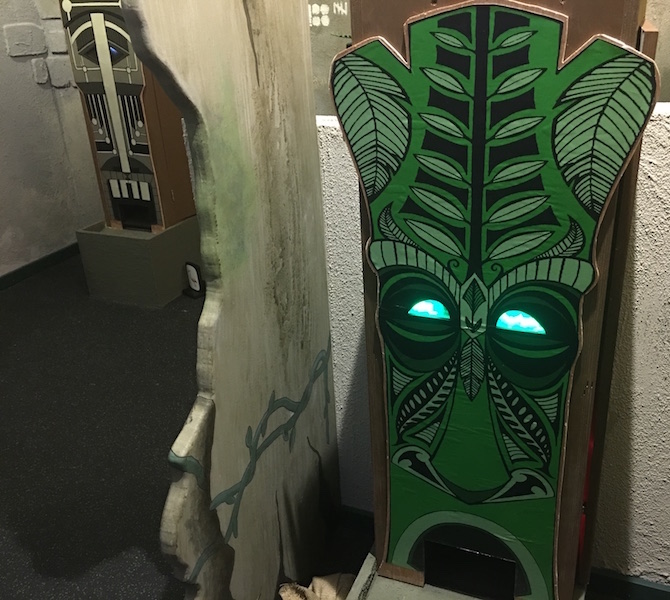 A tiki puzzle dispenser with green glowing eyes.