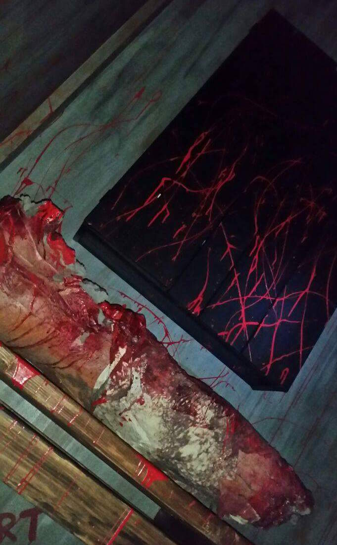 A bloody scene with a mutilated body in a dark room.