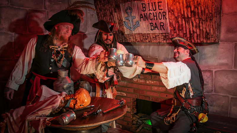 Three pirates sharing a drink in the game's ship.