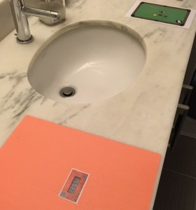 Two puzzle components sit rest on either side of a bathroom sink.