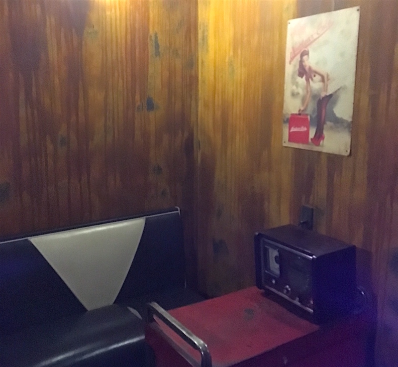 A view of the Vault. There is an old diner bench, a workbench, and a large radio. On the rusty walls hands a picture of a pinup girl.