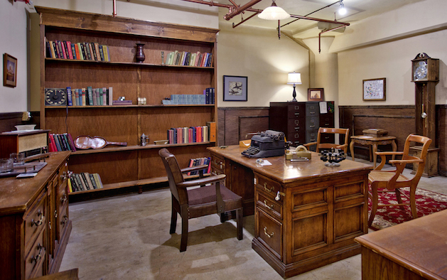In-game, a detective's office with a large desk in the middle, a typewriter, grandfather clock, and large bookcase.